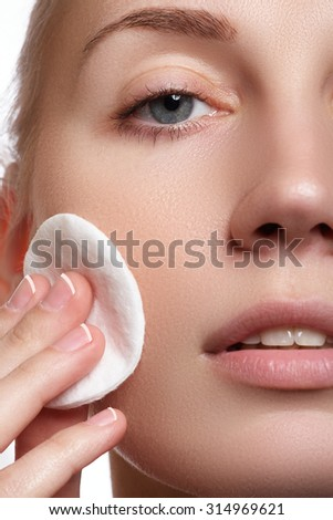 Portrait of happy smiling beautiful young woman cleaning skin by cotton pad, over white background. Cosmetics and healthcare - stock photo