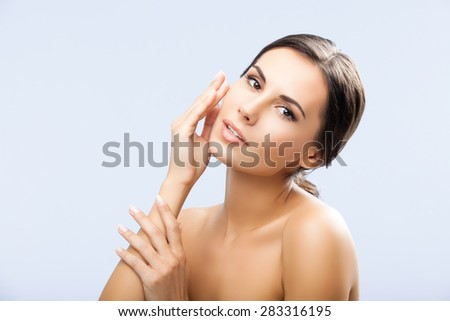 Portrait of happy smiling beautiful young woman touching skin or applying cream, over grey background