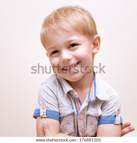 Portrait of happy smiling boy isolated on beige background, studio shot, adorable preschooler, cheerful facial expression, fun and happiness concept