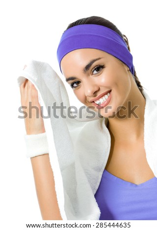 Portrait of happy smiling brunette woman in violet fitness wear with towel, isolated against white background. Young sporty dark-haired model at studio shot. Health, beauty and fitness concept. - stock photo