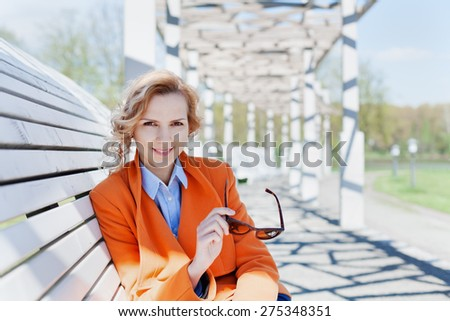 portrait of happy smiling business woman or fashion student with sunglasses sitting on the bench in park, people concept, copy space for text   - stock photo