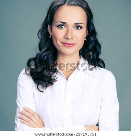 Portrait of happy smiling business woman, over gray background - stock photo