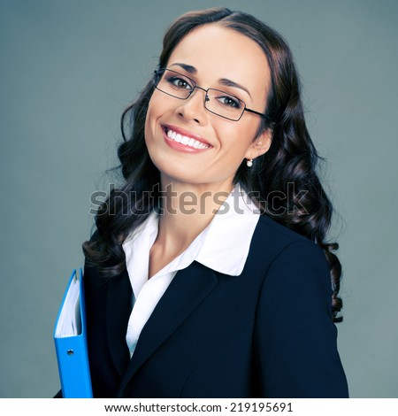 Portrait of happy smiling business woman with blue folder, over gray background - stock photo