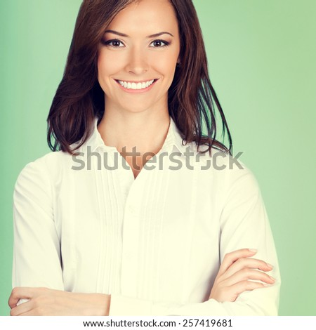 Portrait of happy smiling business woman with crossed arms, on green background - stock photo