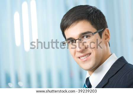 Portrait of happy smiling businessman at office