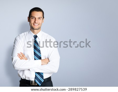 Portrait of happy smiling businessman in crossed arms pose, against grey background. Copyspace blank area for slogan or text. Caucasian male model at studio shot. Business and success concept. - stock photo