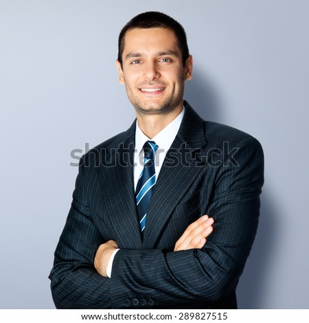 Portrait of happy smiling businessman in crossed arms pose, in black confident suit, against grey background. Caucasian male model at studio shot. Business and success concept. - stock photo