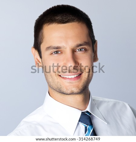 Portrait of happy smiling businessman, posing at studio, against grey background - stock photo