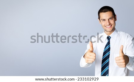 Portrait of happy smiling businessman with thumbs up gesture, with blank copyspace area for text or slogan, against grey background - stock photo