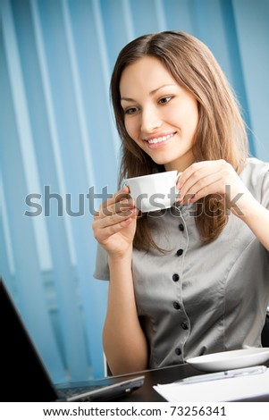 Portrait of happy smiling businesswoman with coffee working with laptop at office