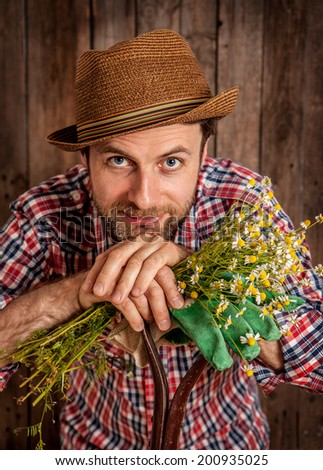 Portrait of happy smiling caucasian forty years old gardener or farmer in a hat holding camomile flowers on rustic vintage planked wood background.