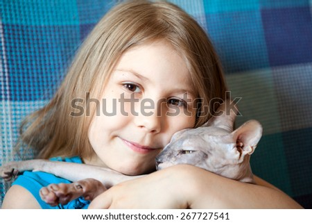 Portrait of happy smiling Caucasian small girl hugging a bald cat, close up view - stock photo
