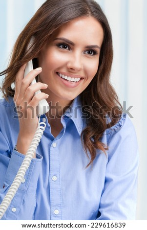 Portrait of happy smiling cheerful beautiful young business woman or support phone worker, at office