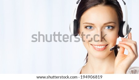 Portrait of happy smiling cheerful beautiful young support phone operator in headset, at office, with copyspace area - stock photo