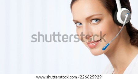 Portrait of happy smiling cheerful beautiful young support phone operator in headset, at office, with blank area for sign or copyspase - stock photo
