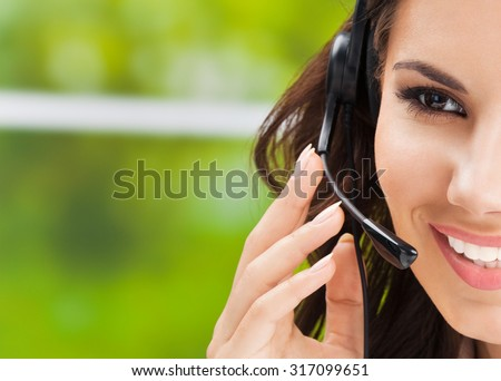 Portrait of happy smiling cheerful beautiful young support phone operator in headset, with copyspace - stock photo