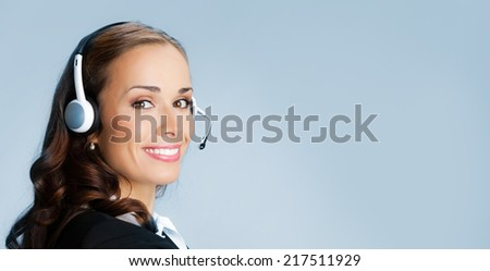 Portrait of happy smiling cheerful customer support phone operator in headset pointing at something, over blue background - stock photo