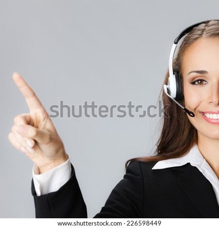 Portrait of happy smiling cheerful customer support phone operator in headset pointing at something, against grey background - stock photo
