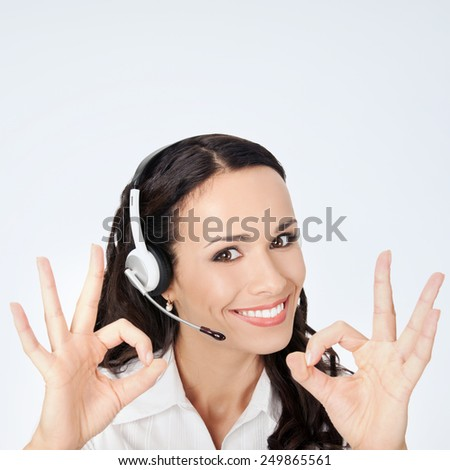 Portrait of happy smiling cheerful customer support phone operator in headset showing okay gesture, against grey background, with copyspace