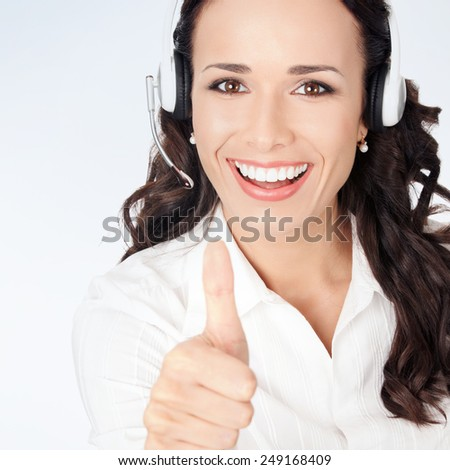Portrait of happy smiling cheerful customer support phone operator in headset showing thumbs up gesture, against grey background - stock photo