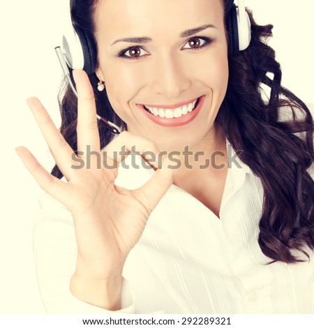 Portrait of happy smiling cheerful customer support phone operator or businesswoman in headset showing okay hand sign gesture - stock photo