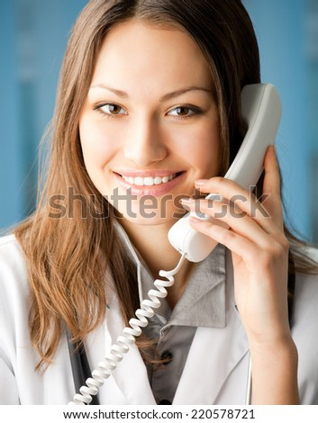 Portrait of happy smiling cheerful young female doctor on phone, at office