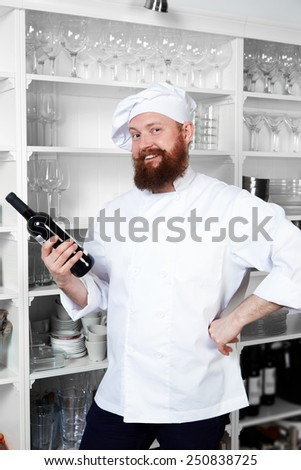 Portrait of happy smiling chef cook holding bottle of red wine in the kitchen - stock photo