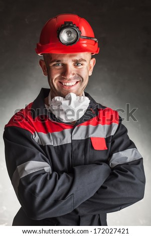 Portrait of happy smiling coal miner with his arms crossed against a dark background - stock photo