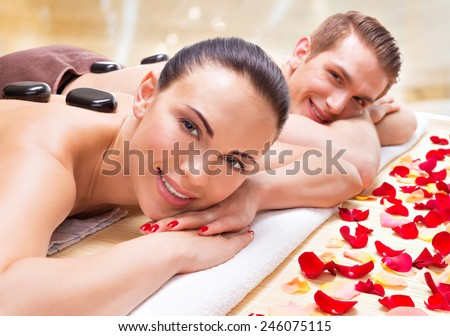 Portrait of happy smiling couple relaxing in spa salon with hot stones on body.  - stock photo