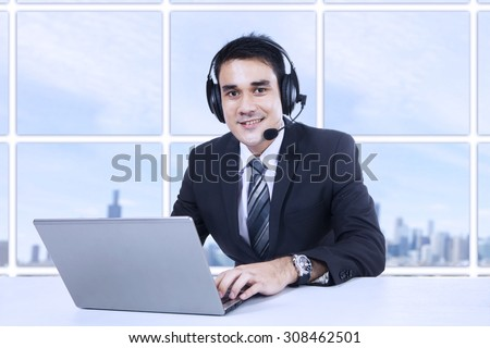 Portrait of happy smiling customer support phone operator in headset at office