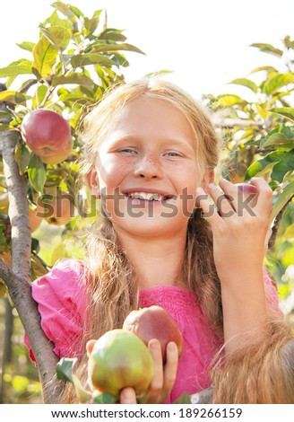 Portrait of happy smiling cute child (girl) with green and red fresh apples near apple tree on beautiful day. Kid eating healthy food outside in summer dress and laughing. Outdoor. Close up. - stock photo