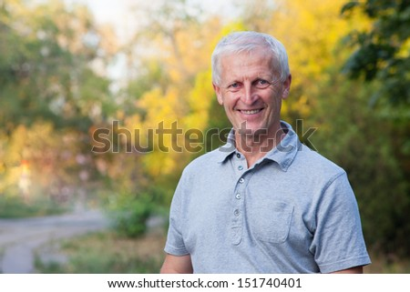 portrait of happy smiling face of grey-haired old man. Outdoor. Blue jeans. Grey t-shirt.