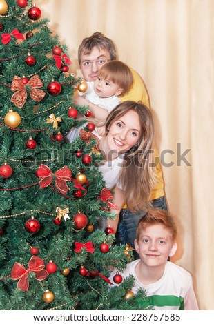 Portrait of happy smiling family by christmas tree. Caucasian family is standing and having fun. Relaxing, positivity family is in the room - mother, father and two sons. Close up. New year concept. - stock photo