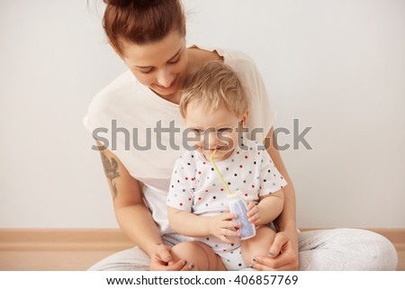 Portrait of happy smiling family. Close up view of attractive young mother with her baby boy wearing pajamas, playing and laughing, sitting against white background at the weekend together.    - stock photo