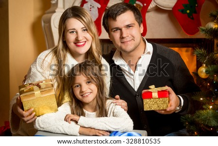 Portrait of happy smiling family posing at fireplace at Christmas - stock photo
