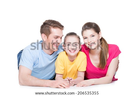 Portrait of happy smiling family with child sitting in colorful shirt lying on the floor at studio - isolated on white. - stock photo