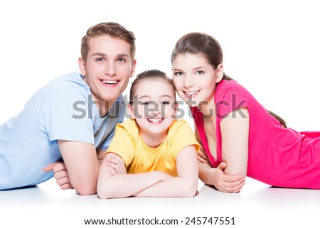 Portrait of happy smiling family with kid sitting in colorful shirt lying on the floor at studio - isolated on white.