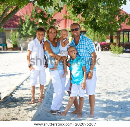 Portrait of happy smiling family with three children standing together in full length. - stock photo