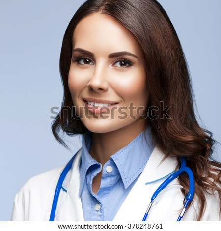 Portrait of happy smiling female doctor, on grey background - stock photo