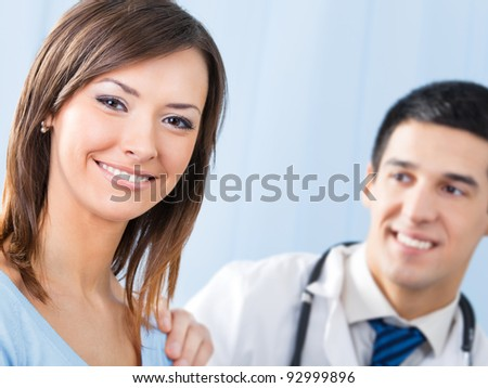 Portrait of happy smiling female patient and doctor at office. Focus on woman. - stock photo