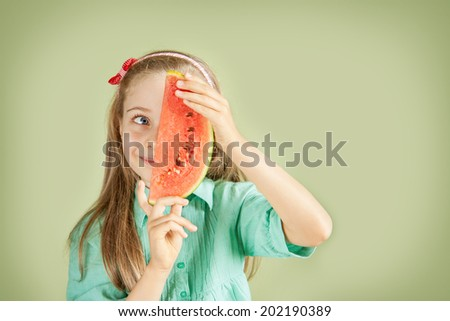 Portrait of happy smiling five years old blond caucasian child girl with watermelon on pastel green background. Careless childhood or healthy diet concept - layout with free text space. - stock photo