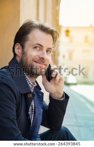 Portrait of happy smiling forty years old caucasian man talking on a mobile phone. Street and city buildings as background. - stock photo