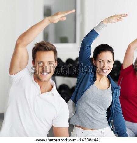 Portrait of happy smiling group with arms raised doing stretching exercise in gym - stock photo