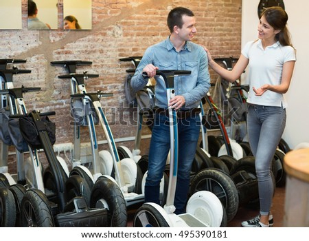 Portrait of happy smiling guy and girl making choice of segways ot rental store