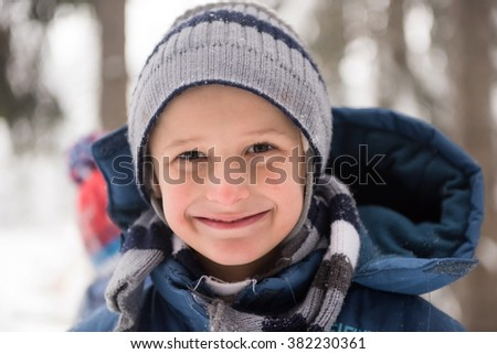 portrait of happy smiling little boy child outdoors having fun and playing on snowy winter day - stock photo