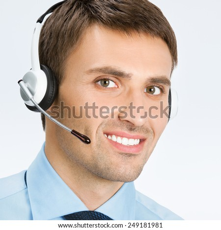 Portrait of happy smiling male customer support phone operator in headset, against grey background - stock photo