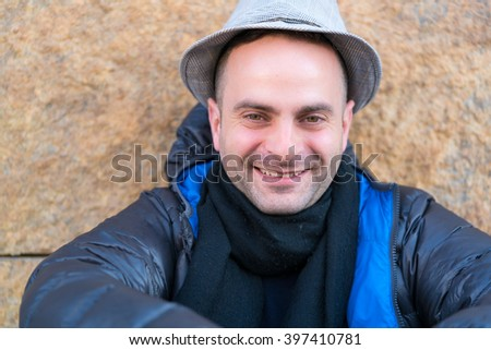 Portrait of happy smiling man looking at camera while sitting on the street against granite wall