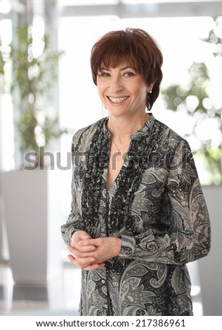 Portrait of happy smiling mature businesswoman, looking at camera. - stock photo