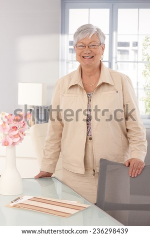 Portrait of happy smiling mature woman at home. - stock photo