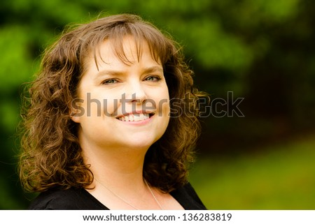 Portrait of happy, smiling middle-aged woman outdoors - stock photo